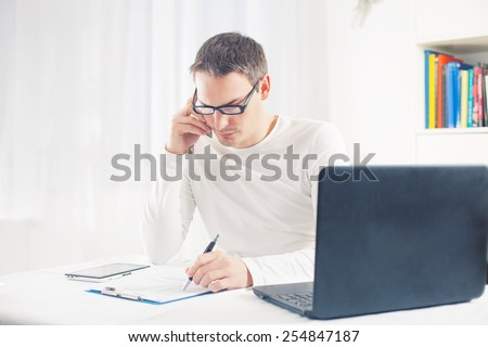 Busy young man talking on mobile phone while sitting in front of laptop looking at paperwork