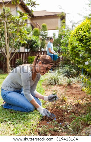 busy young woman and husband working in home garden
