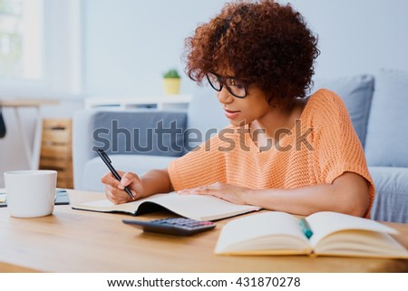Busy young woman learning at home for exam
