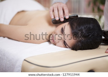 Busy young woman taking a phone call at a spa - stock photo