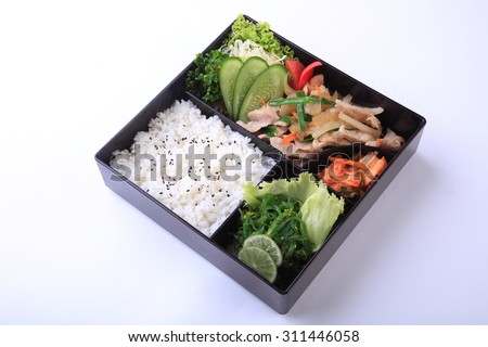 Buta Shoga Bento, stir fried  pork with sauce with rice and seaweed salad in bento isolated on white background. - stock photo