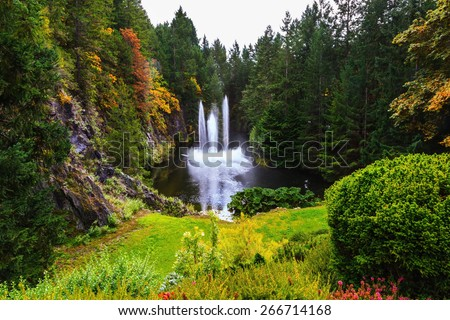 Butchart Gardens on Vancouver Island, Canada. Dancing fountain in a quiet pond. Autumn day in the park - stock photo