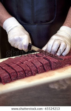 Butcher cutting slices of fresh beef - stock photo