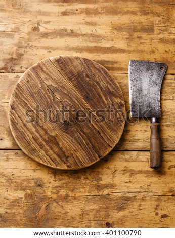 Butcher Meat cleaver and Chopping board block on wooden background - stock photo
