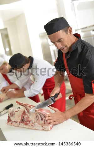 Butcher preparing meat ribs for training class