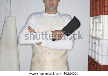 Butcher standing, arms crossed,  Holding Cleaver next to stack of crates, mid section - stock photo