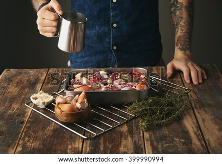 Butcher tattooed hands holds sause pot above metallic stainer with raw meat steaks, ready to pour it with tzatziki Spices and herbs near: garlic rosemary onions Everything on aged vintage wooden table