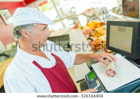 Butcher weighing some meat - stock photo
