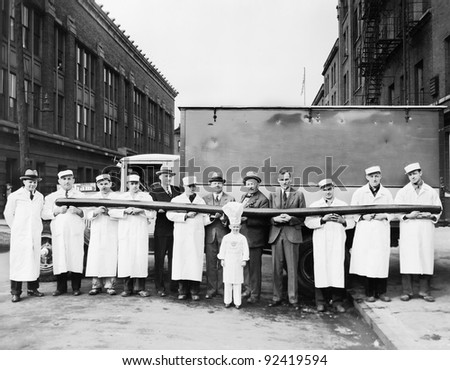 Butchers showing off a long sausage in front of a truck - stock photo