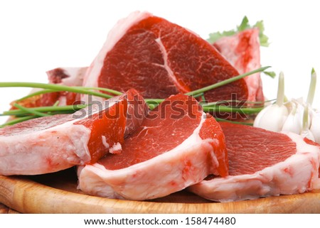 butchery : fresh raw beef lamb big rib and fillet ready to cooking with green stuff on wooden plate isolated over white background - stock photo