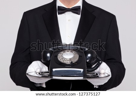Butler holding a silver tray with an old retro black telephone on it.