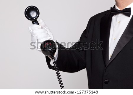 Butler holding the handset from a telephone - stock photo