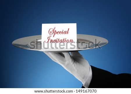 Butler or waiter holding a card reading special invitation on a silver platter- message can easily be changed - stock photo