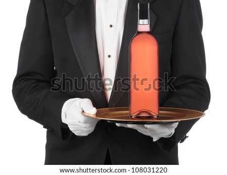 Butler wearing a tuxedo holding bottle of red wine on a serving tray. Horizontal format showing persons torso only. - stock photo