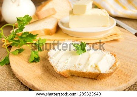 Butter and bread for breakfast, with parsley over wooden table - stock photo