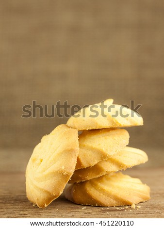 Butter and milk cookies placed stack on wooden table, selective focus with blurred background - stock photo