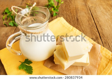 Butter and milk (dairy products) over rustic wooden table - stock photo