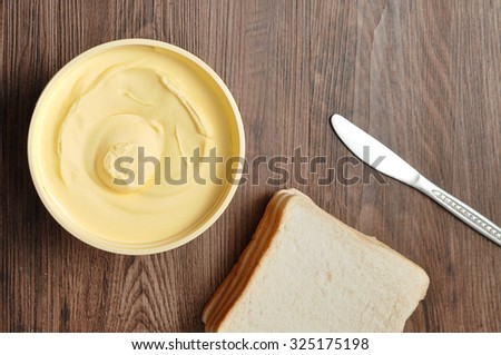 Butter, bread and a knife isolated on a wooden background - stock photo