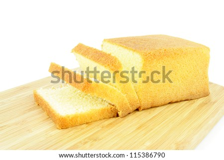 Butter cake sliced on a wooden board. On a white background - stock photo
