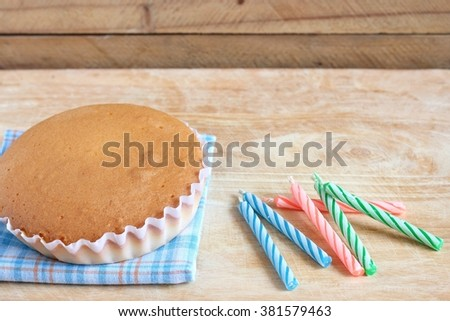 butter cake with sweet candles on wood background