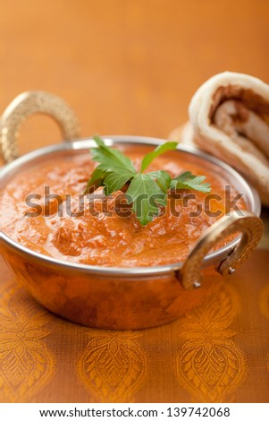 Butter chicken with some naan bread. - stock photo