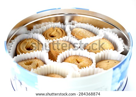 Butter cookies in a tin container, shallow focus - stock photo