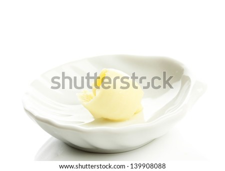 Butter curl on plate, isolated on white