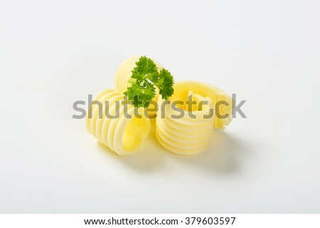 butter curls with parsley on white background