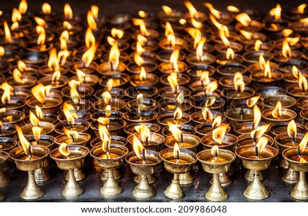 Butter lamps with flames near Bodhnath stupa in Kathmandu valley, Nepal