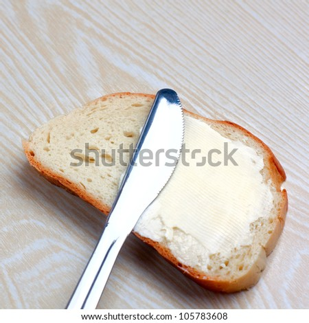 butter on a slice of bread and knife - stock photo