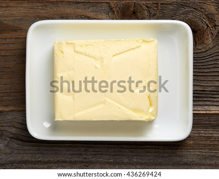 Butter on butter dish on wooden table, top view - stock photo