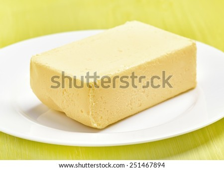 Butter on white plate on green table - stock photo