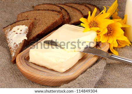 Butter on wooden holder surrounded by bread and flowers on sacking background - stock photo