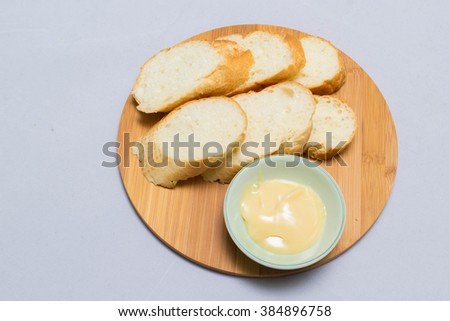 Butter on wooden holder surrounded by bread and milk on natural background - stock photo
