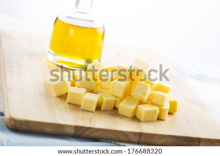 Butter pieces (cubes) on a cutting board, with bottle of vegetable oil in the background - stock photo