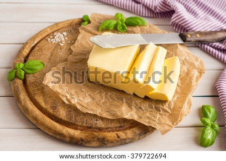 Butter. Slice of butter. Fresh sliced butter on the wooden plate. - stock photo