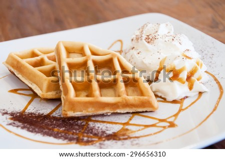 Butter waffles decorated on dish with whipping cream and caramel sauce