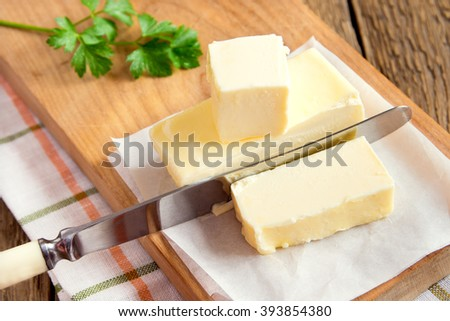 Butter with knife over paper and wooden background