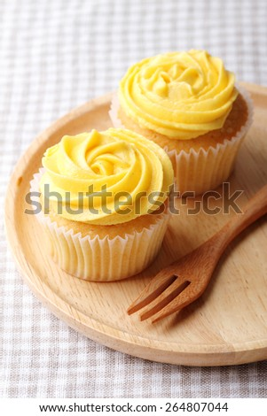 buttercup color frosting cupcakes on wooden plate with fork - stock photo