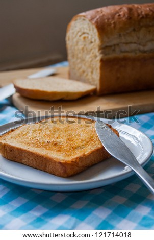 Buttered slice of bread and loaf - stock photo