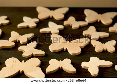 Butterflies of wood on a black wooden background - stock photo