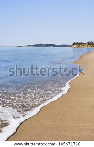 Butterfly Beach in Santa Barbara on a very calm day with Leadbetter Point in the distant background. - stock photo