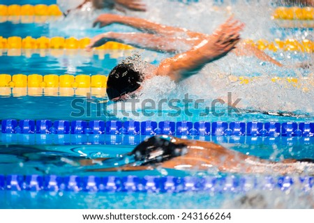 Butterfly men swimming race on swimming pool - stock photo