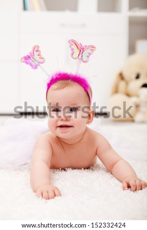 Butterfly princess crawling - happy baby girl on the floor - stock photo