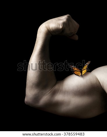 Butterfly Resting on Man Flexing Bicep Muscle on a Black Background