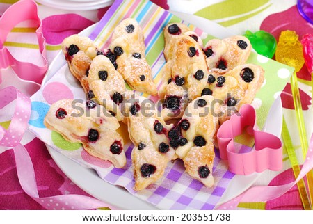 butterfly shaped puff pastry cookies with blueberry for children`s birthday party - stock photo