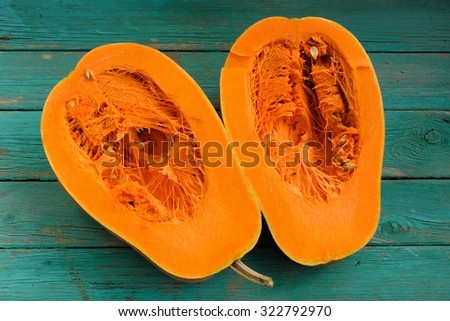 Butternut squash halved on wooden turquoise table - stock photo
