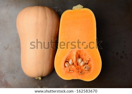 Butternut Squash on a metal cooking sheet. The fruit is cut in half showing both the inside and outside. Horizontal format.  - stock photo
