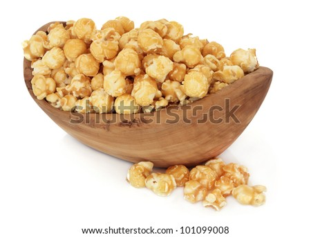 Butterscotch popcorn in an olive wood bowl and loose over white background.