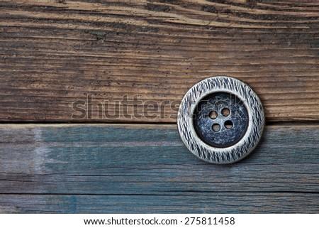 Button for clothes on an old wooden surface of board